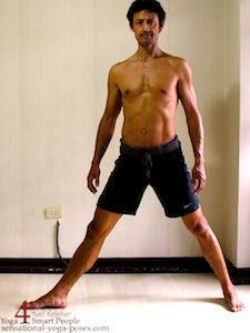 Entering into yoga triangle pose starting with feet separated with one foot turned out 90 degrees and the other foot turned in. Sensational Yoga Poses Neil Keleher