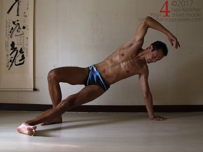 Balancing in side plank pose, both feet on the floor and hips lifted. Neil Keleher. Sensational Yoga Poses.