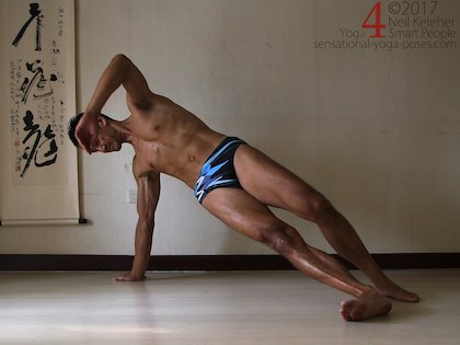 Balancing in side plank, hips lifted, both feet on the floor but weight more on the bottom foot. Neil Keleher. Sensational Yoga Poses.