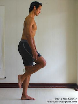 balancing on one leg and slowly bending forwards while keeping the lifted knee pulled forwards. This photo shows the starting position with knee lifted and torso upright. Neil Keleher. Sensational Yoga Poses.
