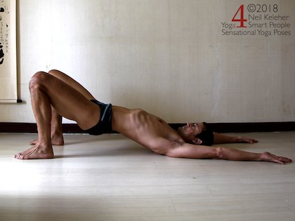 bridge pose with arms reaching past the head as a prep for wheel pose. Neil Keleher. Sensational Yoga Poses.