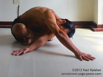 Bending forwards while sitting with the legs crossed, reach one arm across the front of the chest towards the opposite side. Sink that shoulder down towards the floor to stretch the outside of the shoulder. Reach the other arm forwards and lengthen the upper body. Neil Keleher. Sensational Yoga Poses.