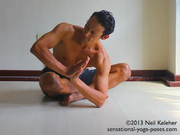 Sitting with legs crossed, bend forwards and place one elbow on the floor. Turn the ribcage towards the opposite side. Place hands together in prayer and position the forearms so that they form one straight line. Press the bottom elbow into the floor. Press the top hand against the bottom hand. Using both shoulders turn and twist the ribcage and spine. Neil Keleher. Sensational Yoga Poses.