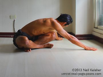 Sitting with legs crossed, bend forwards and then reach both arms to the side. Use the arms to bend the lumbar spine and thoracic spine sideways. Neil Keleher. Sensational Yoga Poses.
