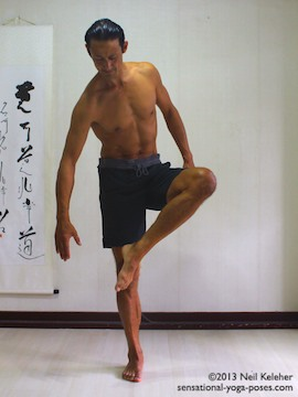 Sensational Yoga Poses, Model Neil Keleher. balancing on one leg while moving into eagle pose with lifted foot in front of the standing leg knee.