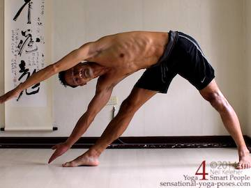 Yoga triangle pose with both arms reaching past the head to the side, neil keleher, sensational yoga poses.