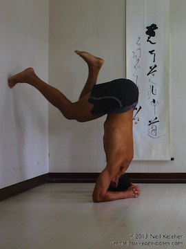 inverted yoga pose, balancing in headstand while using the wall
