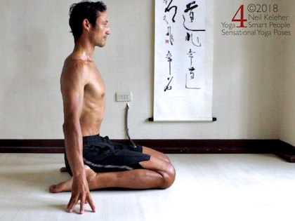 Kneeling Yoga poses: upright  hero. In this seated kneeling position both knees are bent with the buttocks on the floor between the heels. Torso is upright with arms reaching downards and finger tips placed on the floor. Gaze is directed straight ahead. Neil Keleher. Sensational Yoga Poses.