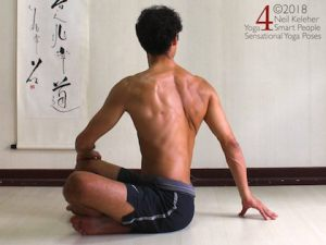 Sitting with legs crossed one hand is placed on the opposite knee. The other hand is on the floor just behind the body. Both arms are being used to turn the ribcage to one side, twisting the spine. Neil Keleher. Sensational Yoga Poses.