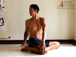 Kneeling Yoga Poses: Easy Bharadvajasana seated twist. In this seated twist one leg is in hero position. The other foot is positioned against the inner thigh of the hero leg. Torso is upright and twisted towards the hero leg side. The hero side hand is on the floor behind the hips. The other hand is on the hero leg knee. Gaze is directed in the direction of twist. Neil Keleher. Sensational Yoga Poses