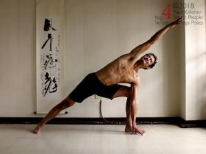 Standing yoga poses: side angle pose with one knee straight and the other knee bent, bent knee han is touching the floor, straight leg arm is reaching past the head, both elbows are straight. Neil Keleher, sensational yoga poses.