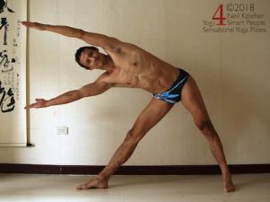 Standing yoga poses: triangle pose with both knees straight, elbows straight and arms reaching past the head. Neil Keleher, sensational yoga poses.