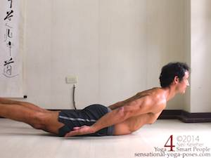 Locust pose (salabhasana) with head, chest and legs lifted.