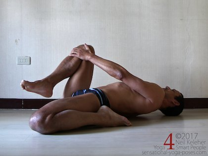 A lying quadriceps stretch variation, hugging one knee to the chest while the other leg is in a kneeling position. Neil Keleher. Sensational Yoga Poses.