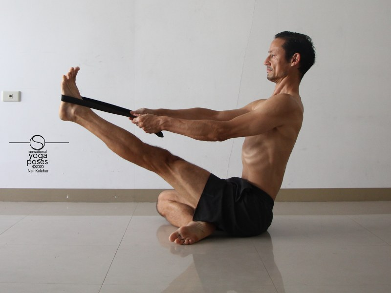 seated hamstring stretching yoga pose with leg lifted and using a belt. Neil Keleher, Sensational Yoga Poses.