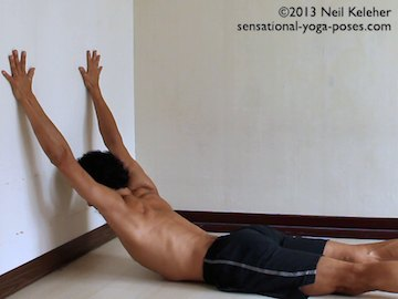 Arm stretches: Prone spiderman arm stretch for front of shoulders and chest. Lying with head towards a wall, arms are reached up the wall while lifting the chest. Spine is actively bent backwards. Shoulders are stretched by sinking the chest down while resisting the hands being pulled down the wall. Neil Keleher. Sensational Yoga Poses.