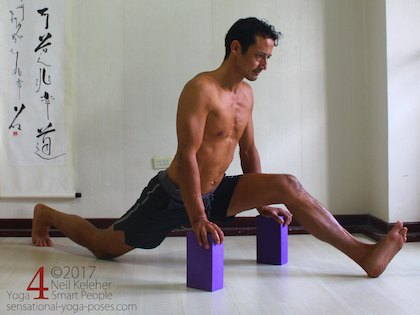 Front to back splits, a forward bend for the front leg with hands on yoga blocks. Neil Keleher. Sensational Yoga Poses.