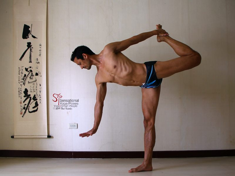 Sensational Yoga Poses, Model Neil Keleher. Balancing on one foot in the dancer position or standing bow with the torso tilted forwards and the other foot being grabbed behind the back. Free hand is reaching forwards.
