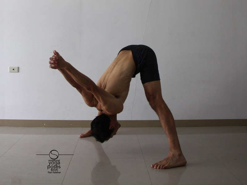 Wide leg standing hamstring stretch with hands clasped behind back (prasaritta padotanasana c). Bending forwards, keep your chest contracted towards your hip bones. Try lifting your sitting bones or pulling down on your ASICs to stretch your hamstrings. Neil Keleher, Sensational Yoga Poses.