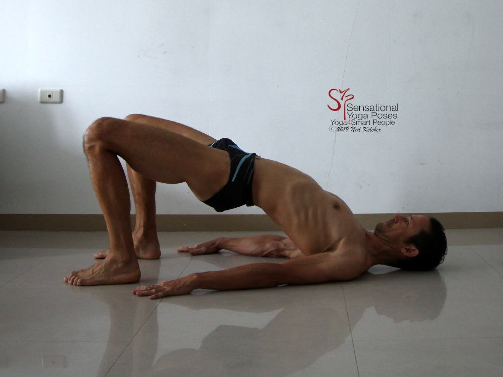 In bridge pose with hips lifted, and belly relaxed. This is in preparation for activating the transverse abdominis. Neil Keleher, Sensational Yoga Poses.