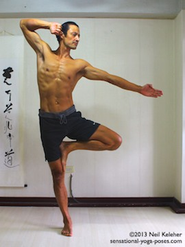 Sensational Yoga Poses, Model Neil Keleher. balancing on one leg in tree pose with the arms in a modified archer position, one arm straight the other arm bent as if pulling a bow string.