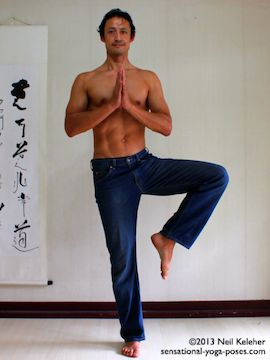 Modified tree pose position balancing on one foot with the other knee lifted to the side but foot is not touching the supporting leg. Hands are in prayer position. Neil Keleher in Blue jeans. Sensaional Yoga Poses.