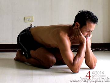 Kneeling Yoga poses: childs pose variation. In this kneeling position elbows are on the floor and hands are cupping the chin. Hips are slightly raised from the heels. Neil Keleher. Sensational Yoga Poses.